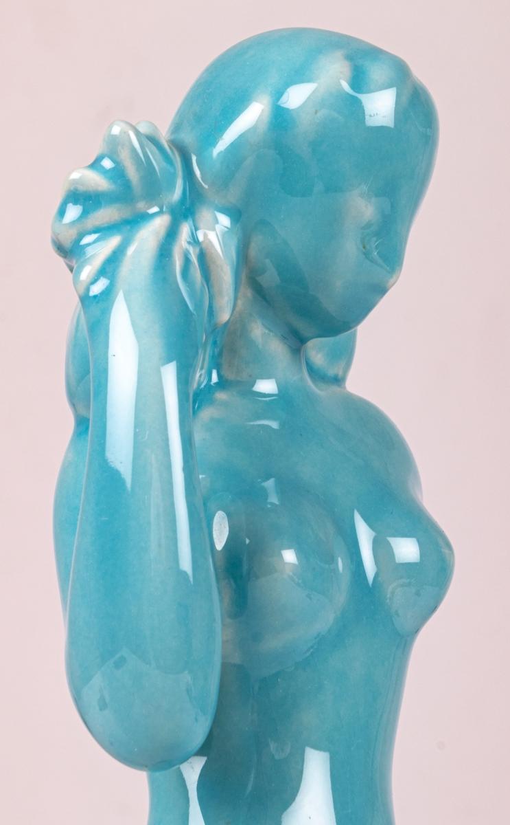 Figurin, stående flicka, höger hand håller en korg med blommor på axeln, vänster hand lutad mot stubbe/buske. Posen och attributen ofta vanlig för att symbolisera ymnighet. Turkos glasyr. Stämpeltryck med Gefles logga med tre rundugnar på undersidan.