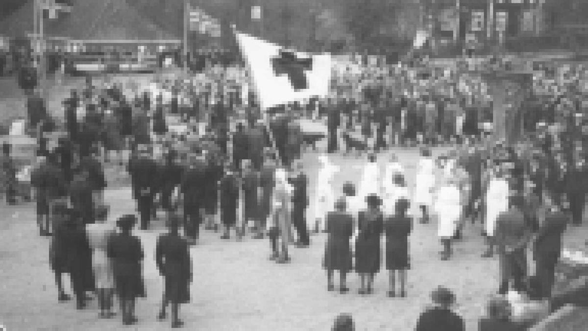 Eydehavn torv, 17. mai 1945 Vi ser murgårdene, norske flagg, Røde kors flagg og hvitkledd personell og mye folk