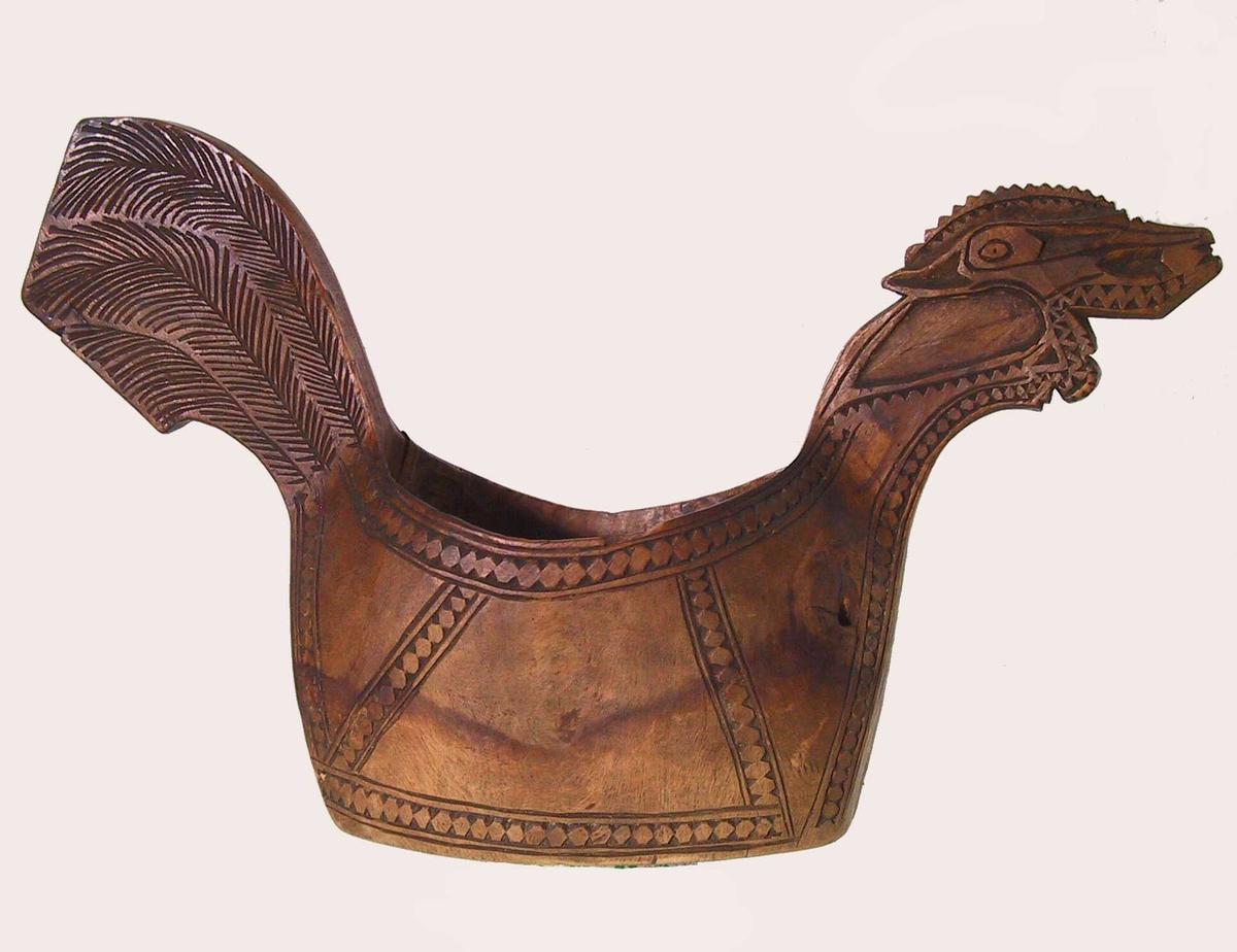Bjerk, skåret  som høne eller hane med stilisert hode, geometrisk bord langs alle konturer.   Innskrift, under bunnen med årstall og initialer.