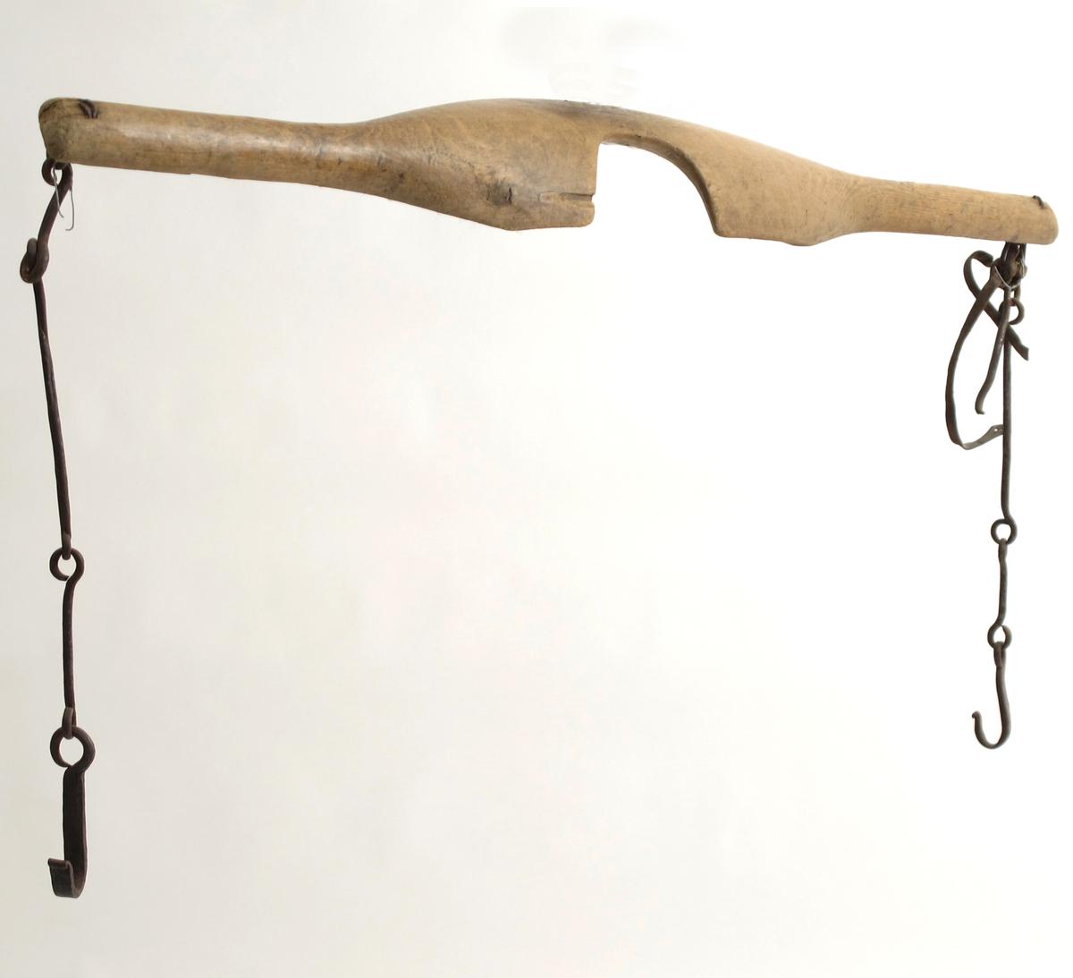 Vassåk, skåert av løvtre.  Langt trestykke med ovalt skålformet midtstykke  med en halvrund innskjæring til nakken. I hver  ende en   jernring  med fireleddet krok. I den ene siden også en smal  lærrem. På den buede side Innskåret:   T. U.  Tilstand: god, krokene rustne.