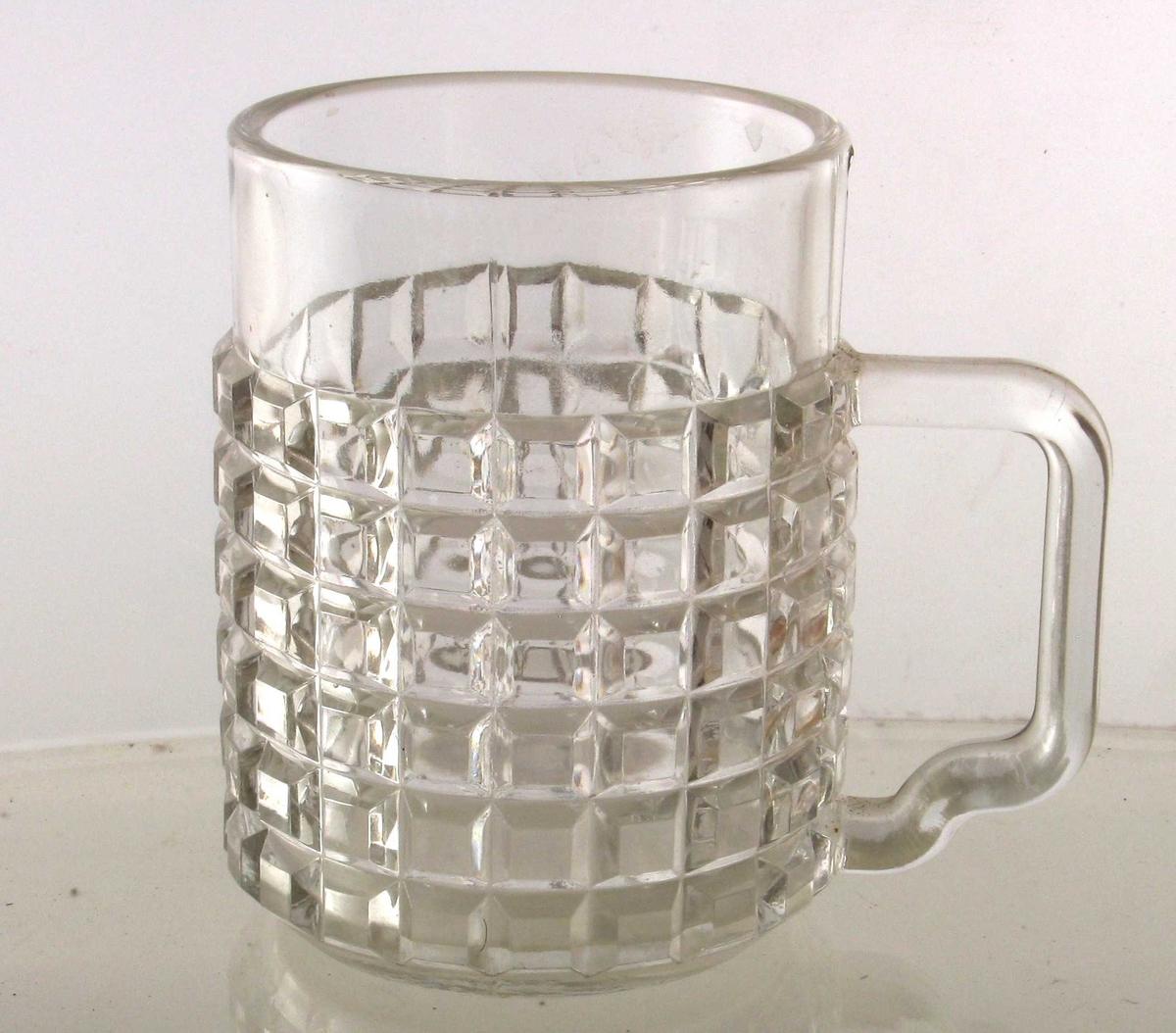 Krus av pressglass.    Sylindrisk bredt glass med hortsontal/  Vertikalrutet nedre del, glatt øverst.  Knekket hank.   Tilstand: god.