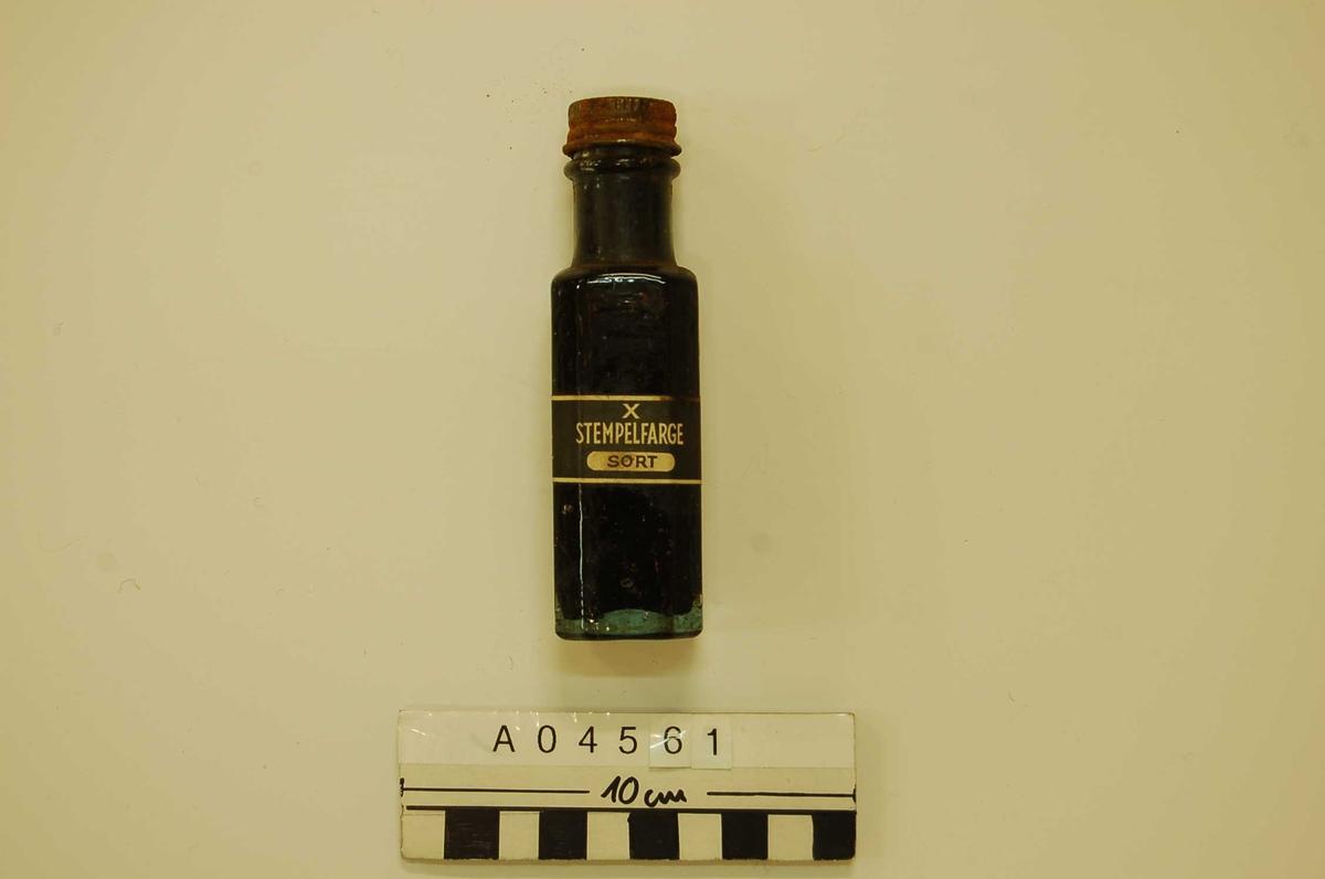 Firkantet glassflaske; klar med metall skrulokk (rustent), inneholder sort stempelfarge.