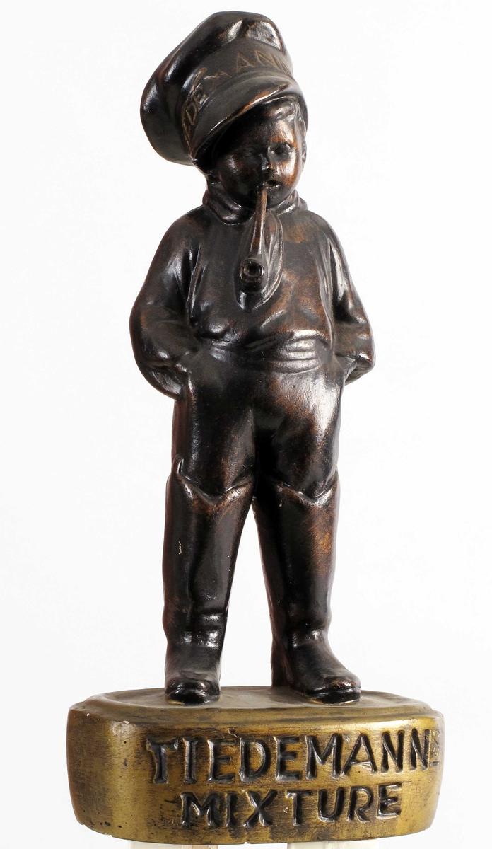 Liten gutt i sjøstøvler og sjømannslue, hendene i bukselomm