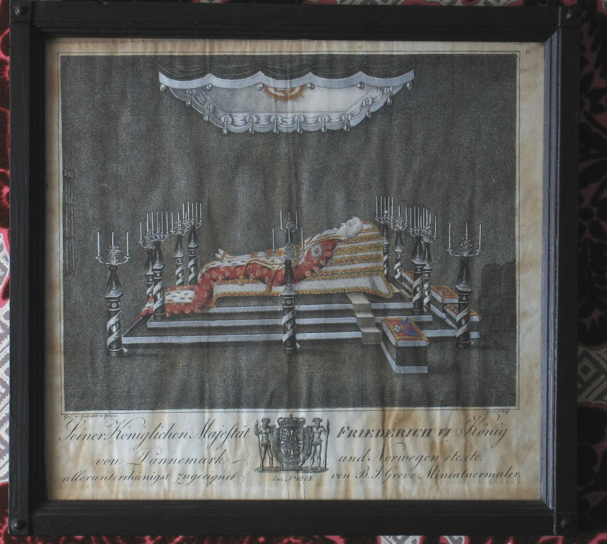 Konge på likstrå. Portrett av Christian VII, (1749 -1808), konge av Danmark Norge.  på paradeseng som lik.  Liggende mann, profil venstre, helfigur,  iført hvit parykk, gullbesatt hvit silkedrakt, hermelinsforet rød kåpe med gylne kroner, ligger på en stabel hvite gullkantede silkeputer,  på sort katafalk  kantet med sølvfrynser, den er omgitt av 12 floromvundne sølvkandelabre på sortmalte  sokler. Kongens ordener utstilt på røde puter kantet med gull, på taburetter  ved døden,  Baldakin av sort stoff kantet med sølvfrynser, over katafalken,  med gullglorie i midten.  De forenede riker, våpen med villmennene under stikket. sammen med dette står dedikasjon.