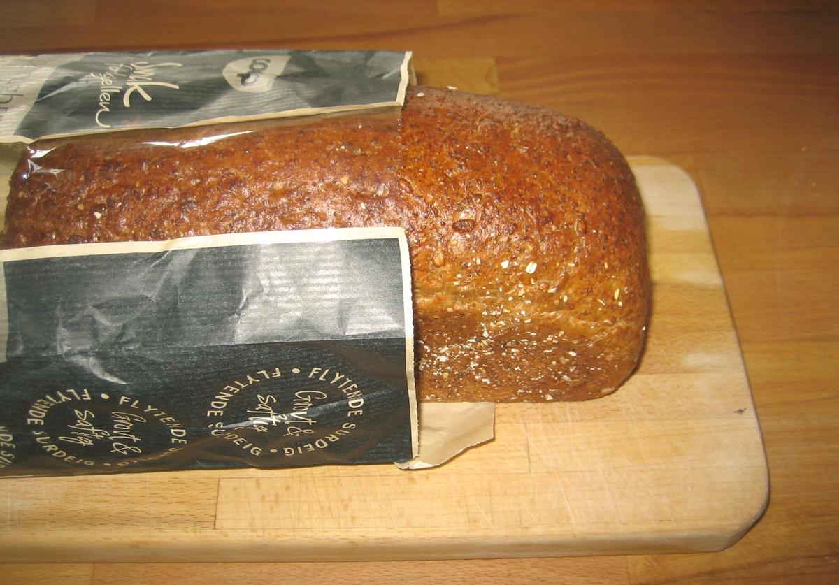 Motiv på posen er brød. Det ligger to skiver foran et oppskåret brød.  Ved siden av brødet er en bolle med smør, der det er plassert en kniv.