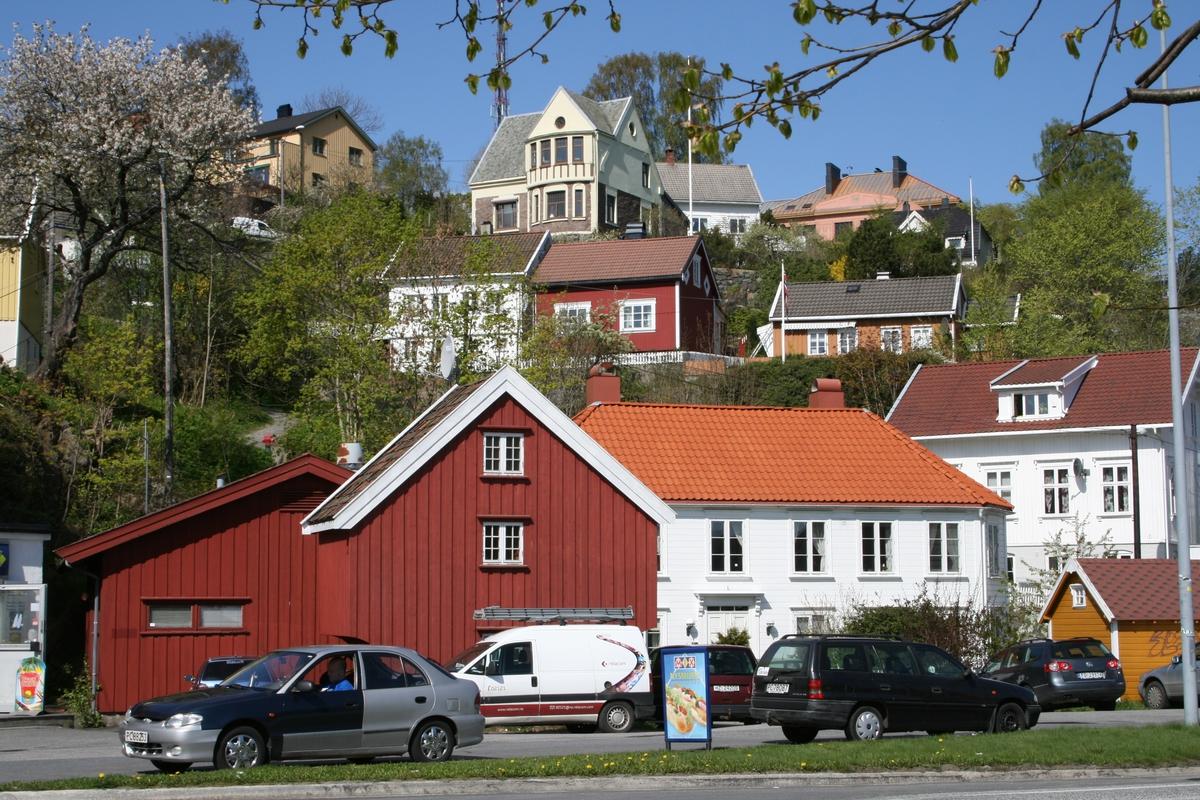 Bebyggelse i strandstedet Barbu. Kjøpmannsgård og gammel sjøbod. Sjøen sto inn til det røde huset sentralt i bildet. I bakgrunnen bebyggelse ved Skydebaneveien, bl.a. Barbu skole.
