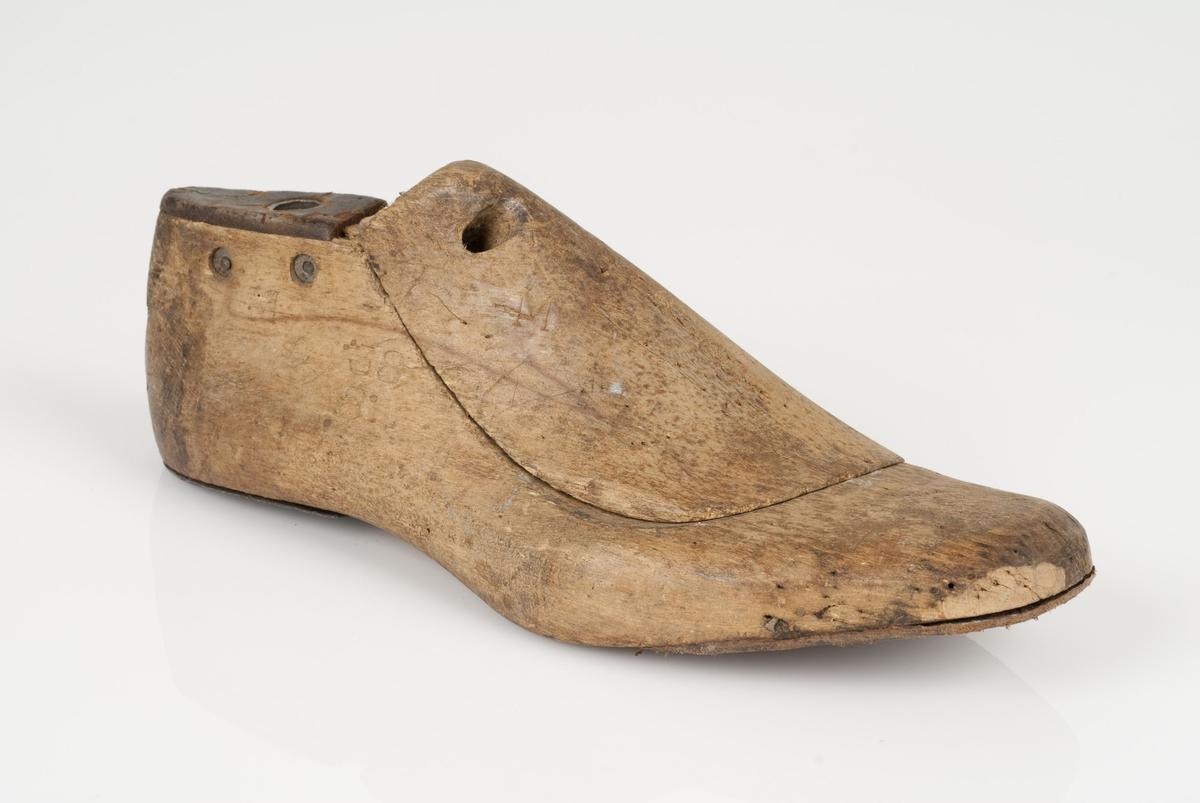 En tremodell i to deler; lest og opplest/overlest (kile). Høyrefot i skostørrelse 38, og 8 cm i vidde. Hælstykket av metall. Lestekam av skinn