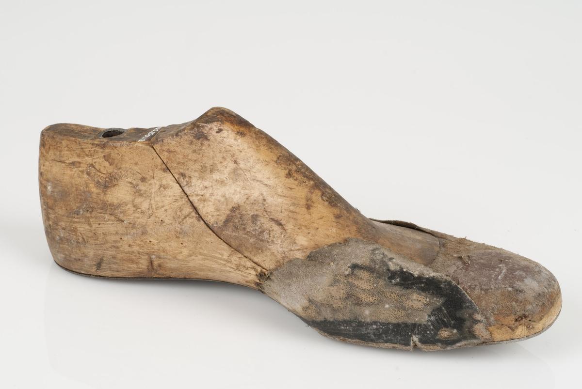 En tremodell i to deler; lest og opplest/overlest (kile). Venstrefot i skostørrelse 38, og 6 cm i vidde. Såle av metall.