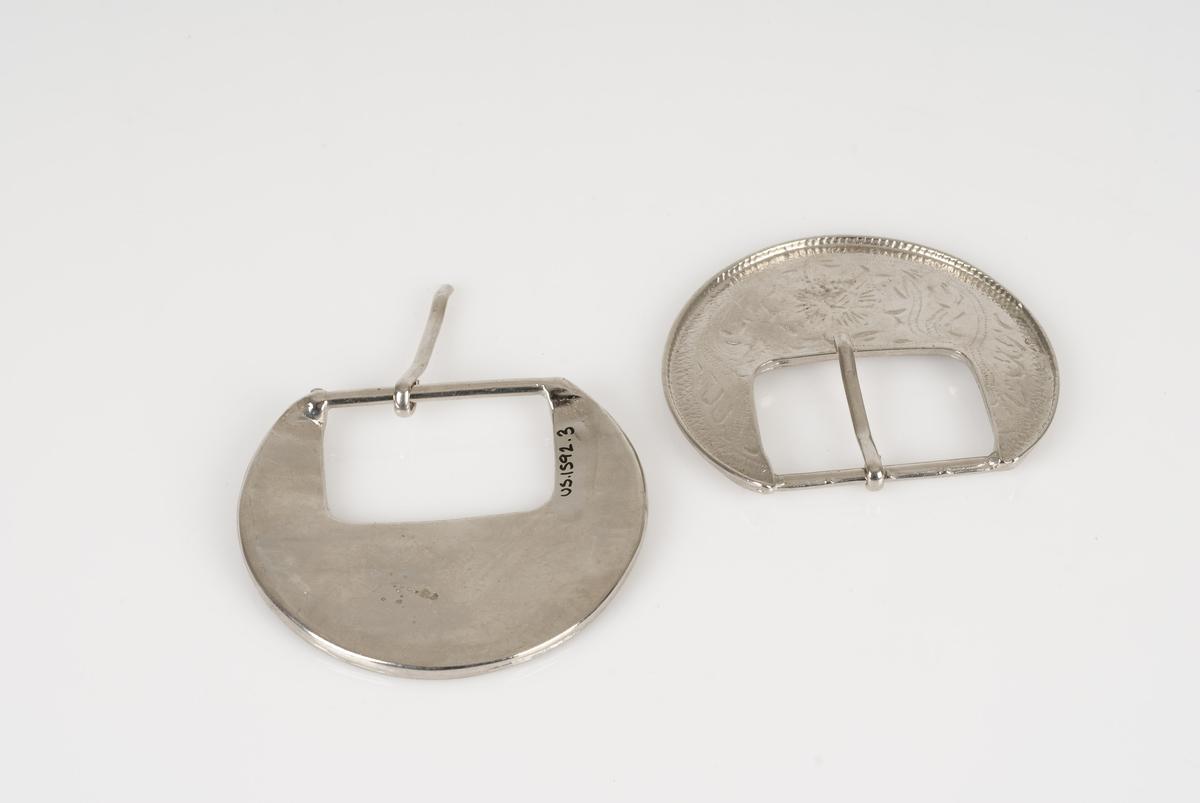 Beltespenne (A-B) av metall. Beltespennene er runde med inngraverte mønstre.