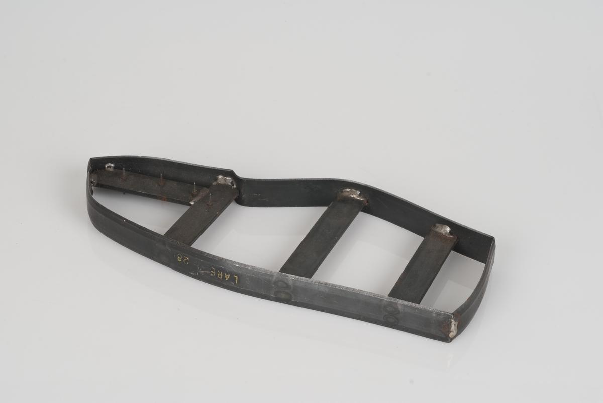 En stansekniv av stål. Stansekniven brukes til å stanse ut skodeler for sko i størrelse 28.