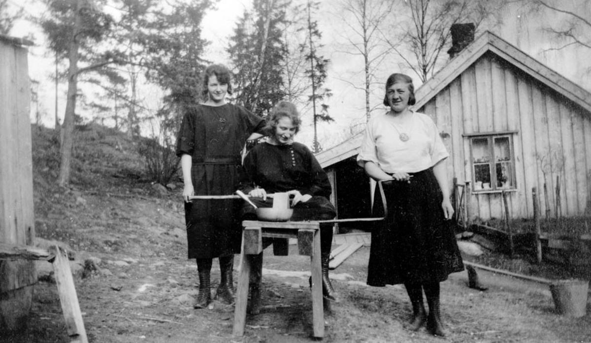 Inga, Helga og Marie Sørlie ved slipesteinen.  Sørlihuset bak.