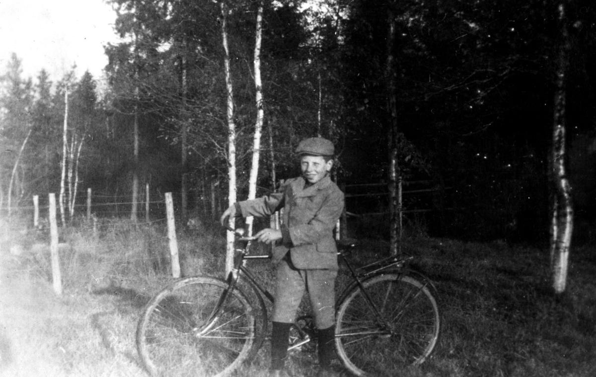Gutt med sykkel blandt bjerkestammene.