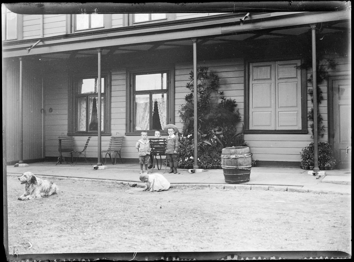 Erik, Arne Emil og Gunnar foran husvegg, utkledd i penklær. Et barn leker på bakken. En hund til venstre i bildet.