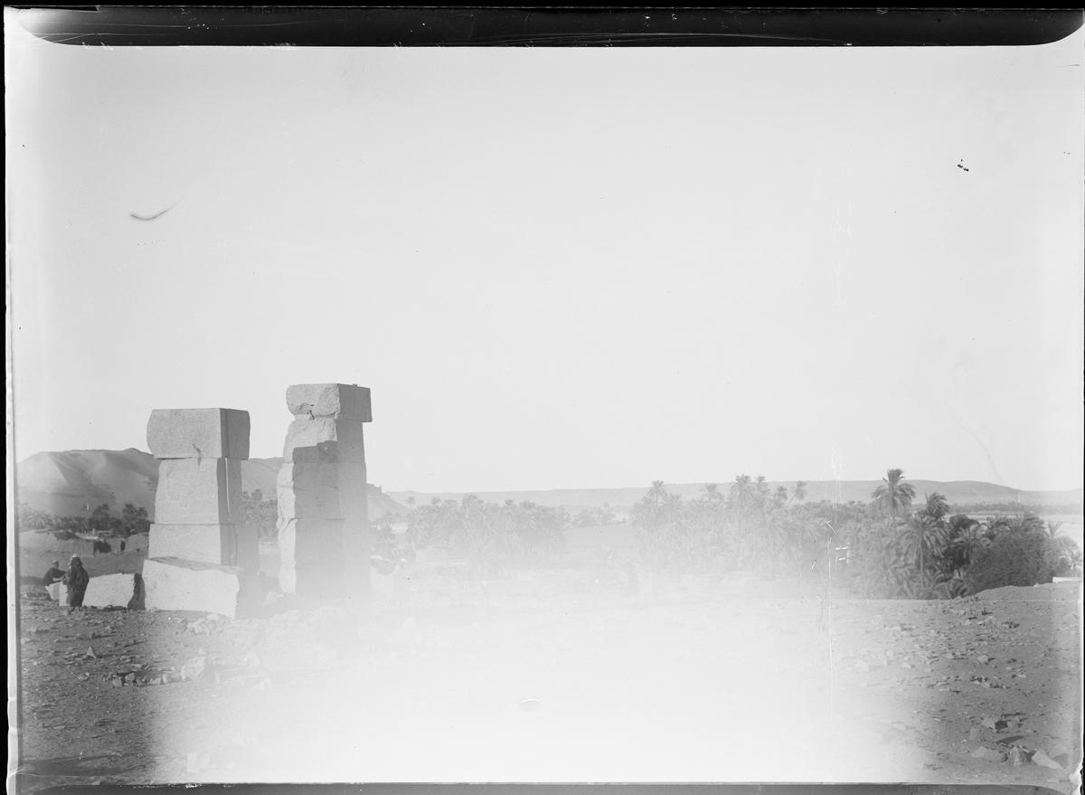 Skadet bilde. Steinruiner og en oase i bakgrunnen.