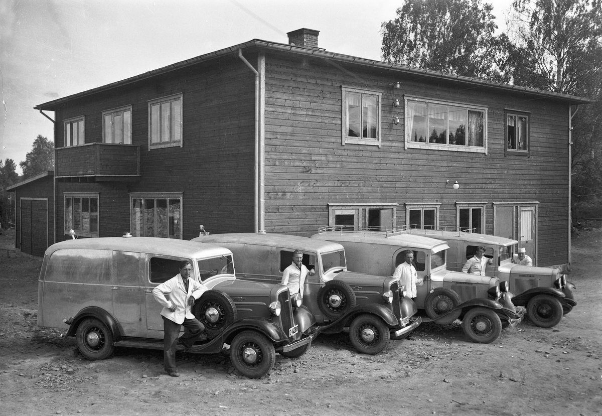 """Utenfor et bakeri. Fire Chevrolet kasse-/varebiler med kjennetegn C-14288, C-14092, C-14369 og A-18305. 13.05.2013: De to nærmeste Chevroletene er årsmodell 1936. I Norges Bilbok 1935 står C-14369 på en Chevrolet 1933 varebil tilh. Albert Haugan, Fjellstrand, Nesodden. Det kan stemme med bil nr. 3 fra v. Den har buet dørprofil karakteristisk for varebiler bygd av N. Jacobsens karosserifabrikk, men også benyttet av Automobilfabrikken og M. Urianstadstads karosserifabrikk, som nettopp holdt til på Fjellstrand. Kilde: Asbjørn Rolseth: Håndverk på hjul. Der er det på s. 595 foto av samme C-14369, men med annet farveskjema og påmalt tekst: """"Albert Haugan. Bakeri og konditori. Fjellstrand tlf 17"""". A-18305 var en Chevrolet 1931 varebil, tilh. Peder Olsen, Thv.Meyers gt. 47, Oslo iflg. Bilboken 1935. Bildet er trolig tatt da de to 1936-modellene (og funkishuset?) var nye, neppe på 50-tallet. Skrevet av: Ivar E. Stav <ivar.es@online.no>"""