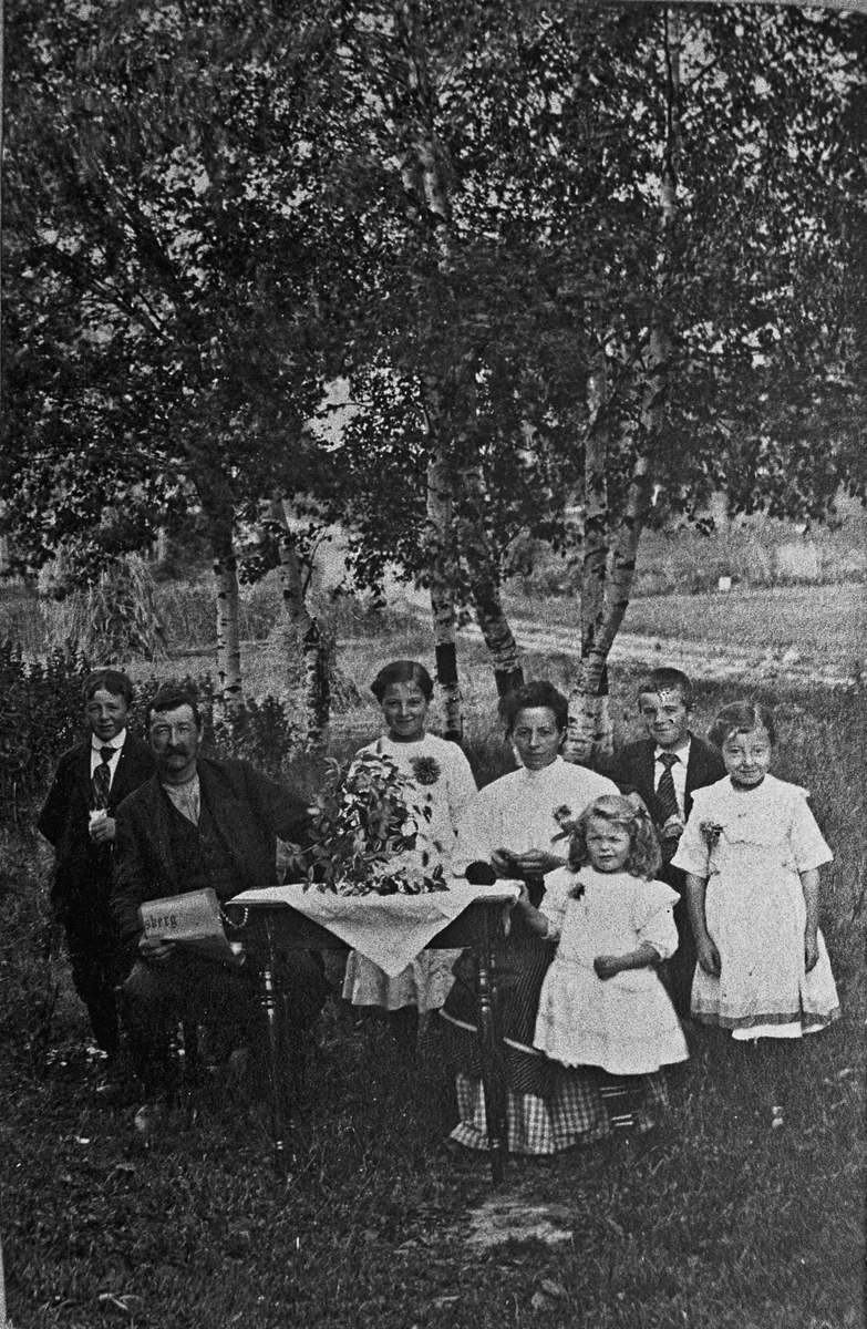 Familie på 7 ved et bord i hagen.