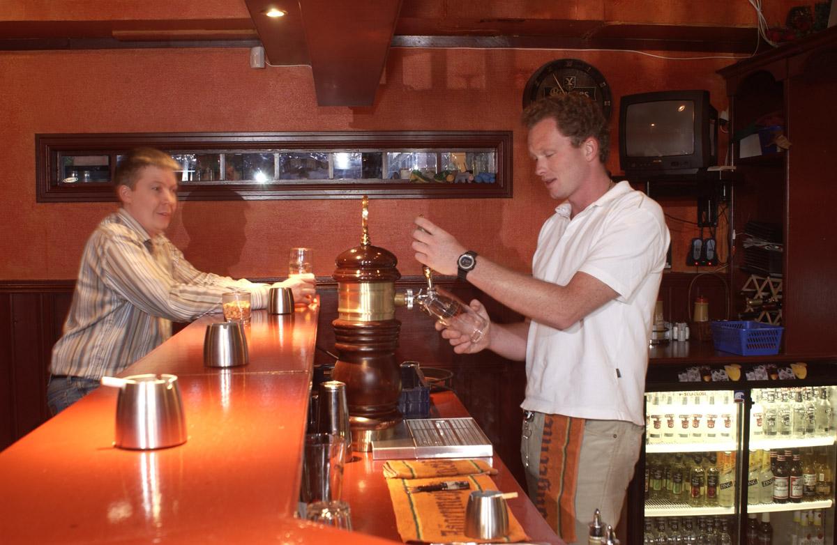 Gjest og bartender med sigaretter. Sveaborg Bar & Spisested ved bardisken