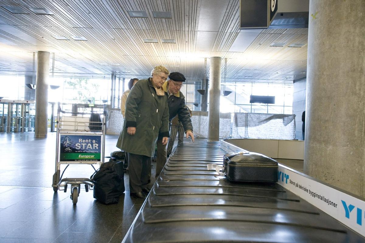 Vesker. Bagasjeutlevering innland. Reisende ektepar venter på bagasjen ved bagasjebåndet. Fotodokumentasjon i forbindelse med dokumentasjonsprosjekt - Veskeprosjektet 2006 - ved Akershusmuseet/Ullensaker Museum.
