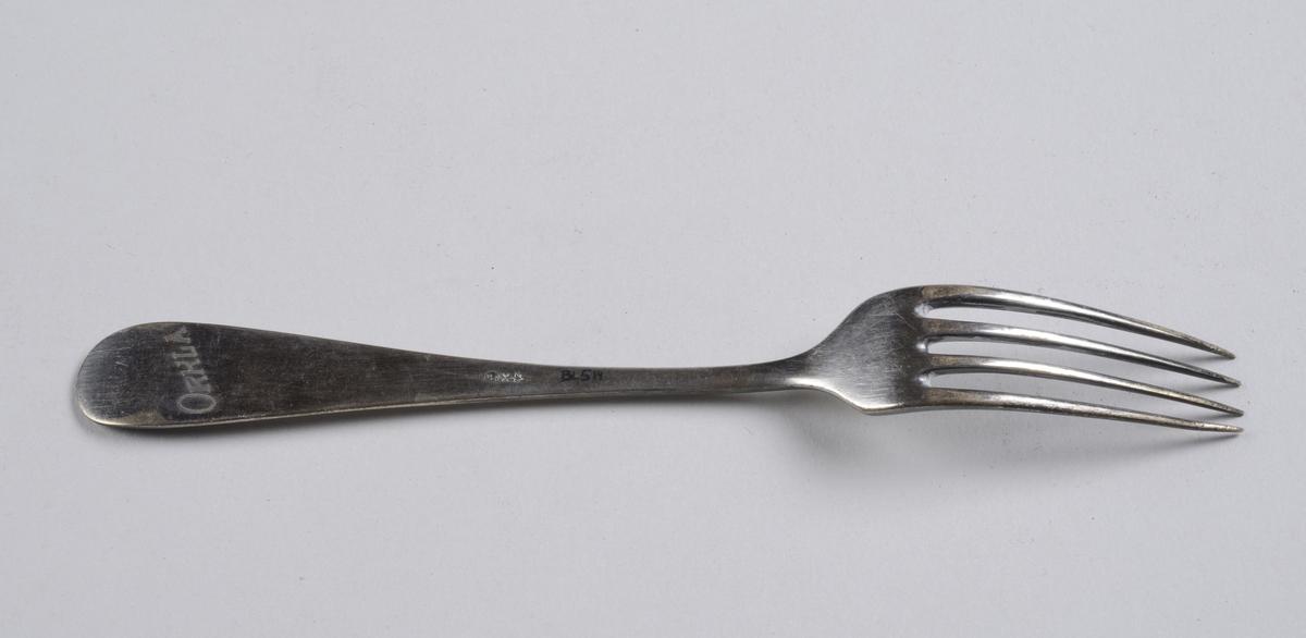Gaffel med lange tenner, og håndtak som er bredest på enden. Enden går litt opp. Enkel dekorasjon i form av en midtstilt opphøyning på enden av skaftet.