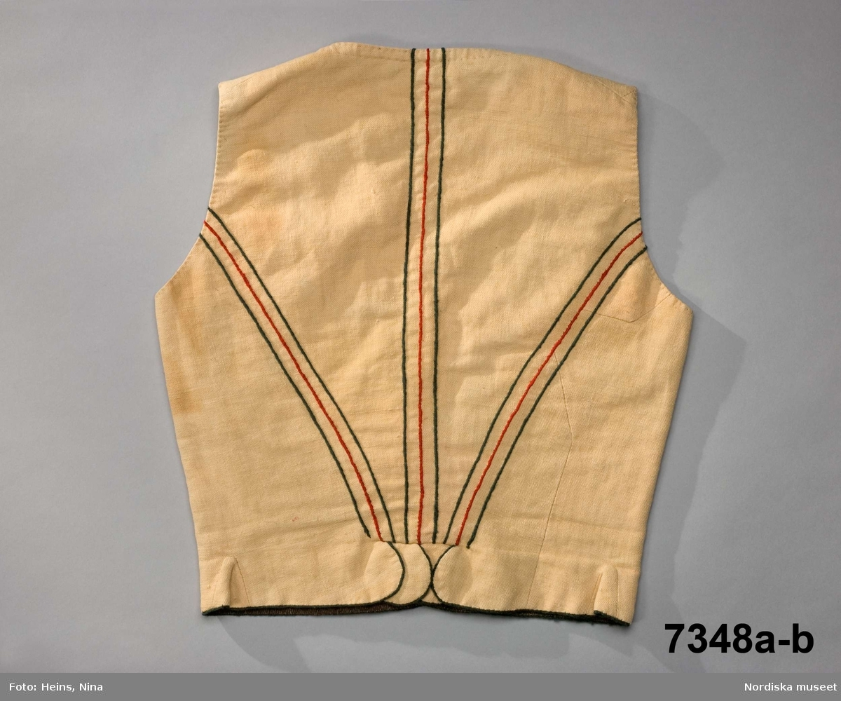"""a.Livstycke som sytts upp på beställning för att visa ett äldre dräktskick. Livstycket är i en modell från tidigt 1800-tal men i material från sent 1800-tal och inte helt exakt återskapat, t.ex finns ingen mittsöm i ryggen. Av ljusgult halvbomullstyg i varpkypert. 2 framstycken/sidstycken, ett ryggstycke. 3 sömmar har markerats i ryggen med vid varje ställe 2 gröna och en röd linje, snodda av  ullgarn och nedsydda med läggsöm. I sidorna infällda skörtkilar och mitt bak skört med 3 runda överlappande skörtflikar. I framkanterna insydda träspröt på gammalt vis, liksom snörning med 5 par snörhål tränsade med grågrönt lingarn. Dekorstickningar med samma garn runt snörhål och vid halsringningen. Snett upp på båda framstyckena en broderad stram """"blomma"""" i rött ullgarn och grågrönt lingarn. Stjälken är en ullgarnssnodd nedsydd med läggsöm. Fodrat med ett brun-och vitmelerat bomullstyg i tuskaft. b. Tillhörande snodd för snörning, av rött, grönt och vitt ullgarn med en trädnål i änden, hoptvinnad av vitmetalltråd. Har sannolikt tillverkats av skräddaren Johannes Boberg tillsammans med en grupp plagg som i bilaga har uppgiften: """"För samlingarna bestälda drägter"""". /Berit Eldvik 2008-03-27"""