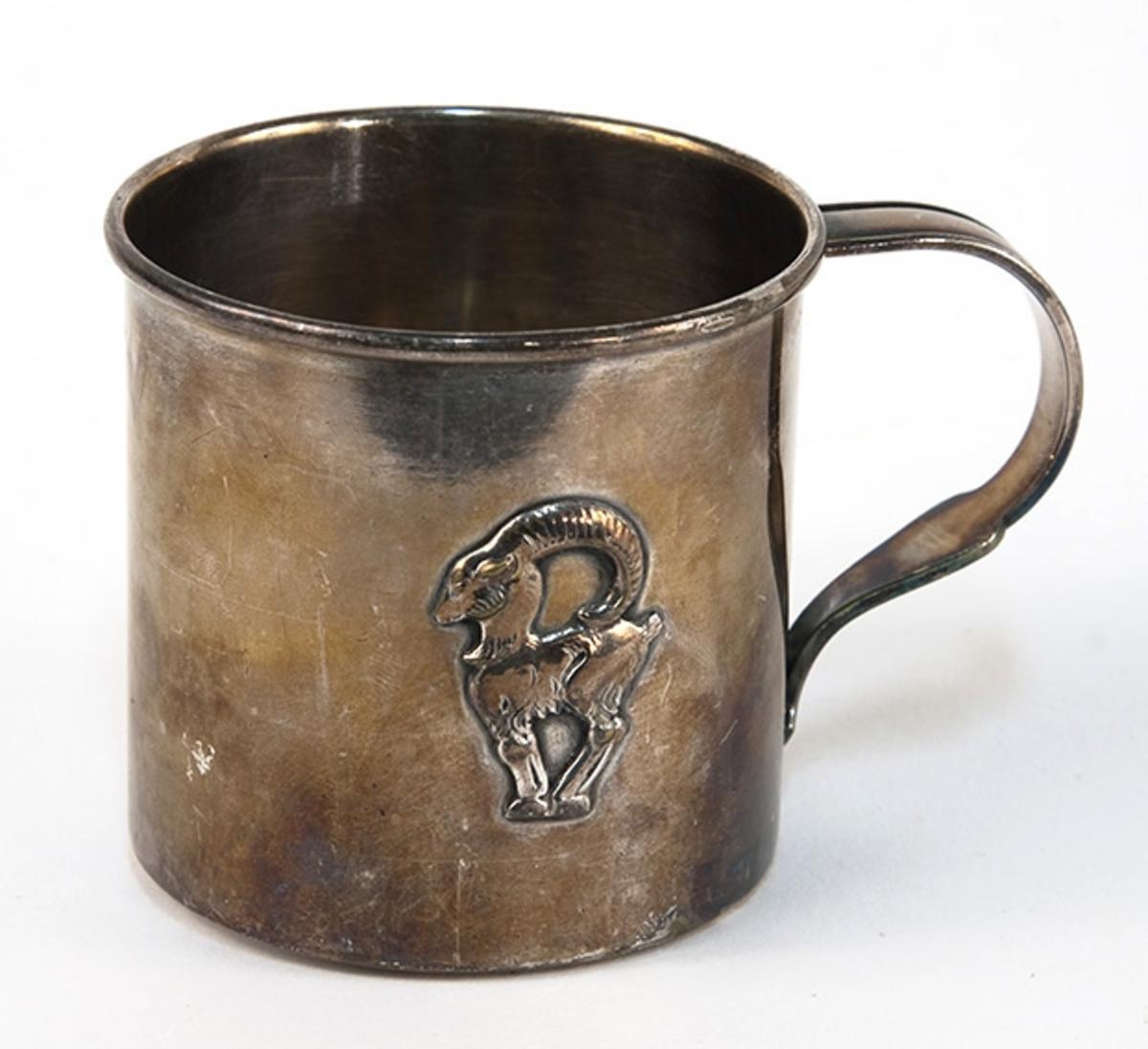 Dåpskrus. Dyrefigur på siden (stenbukk). Gravert tekst Snorre 22-3-42. Sølv eller sølvplett.