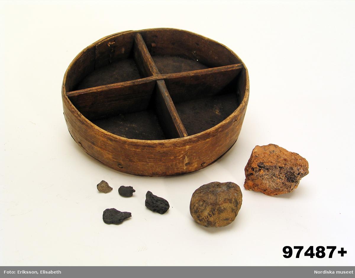 """Huvudliggaren: """"+ Trollask med varjehanda inneh. Av trä, rund, delad i fyra fack. Från Bysjötorp. Ink. 31/12 1903 Gm Keyland, N., kand., Stockh. [Brukningsort:] Västmanland Hjulsjö sn. [Insamlingsnummer] 660.""""  Katalogkort: """"I fyra fack. Innehåller en tegelstensbit, ett litet stycke kvarts, en rund sten, ...""""  Lena Kättström Höök 2019-04-26"""