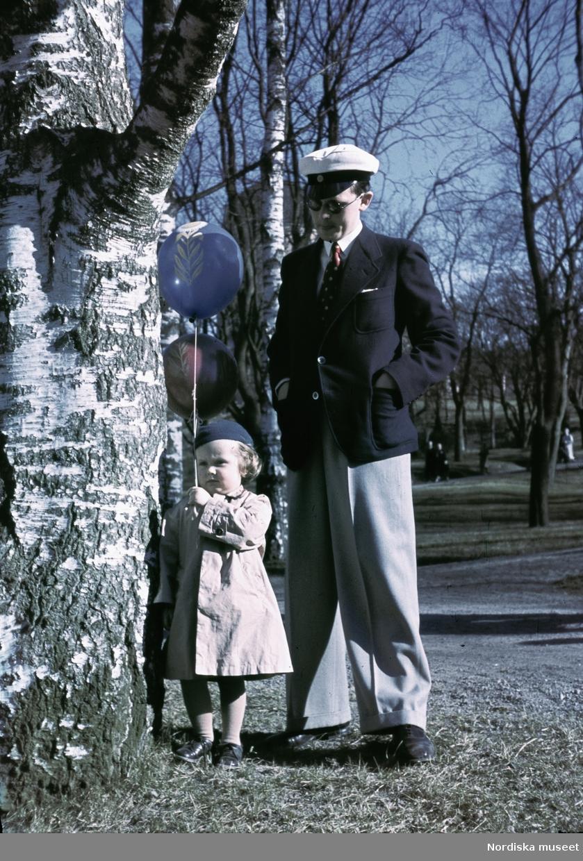 En man med studentmössa och solglasögon och en liten flicka med ballonger.