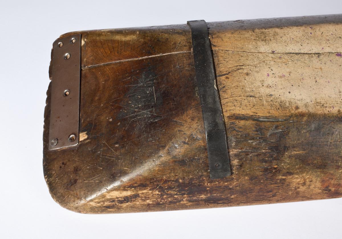 Smalt, avlangt trau med skrå vegger og jernbeslag på undersiden.