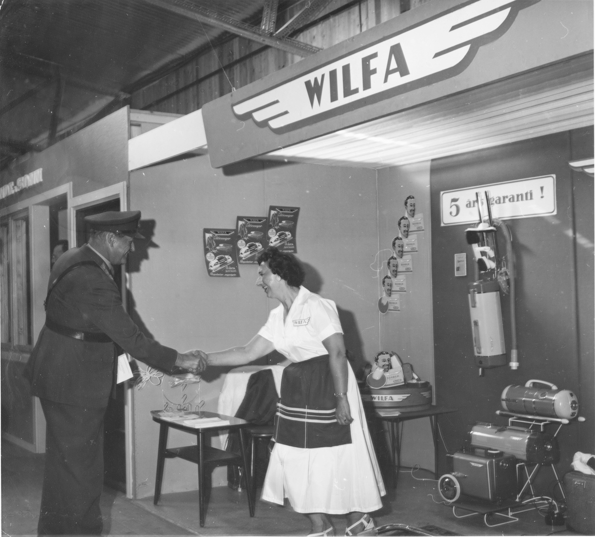 Kong Olav hilser på en dame som står på Wilfa sin stand i forbindelse med en firmautstilling / varerepresentasjon.