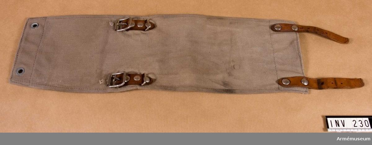 Sydd i gråbrungrön smärting. På kortsidornas insidor skinnskodd. Läderremmar, 120 mm långa, två st. Spännen, två st, för damaskens fastsättning kring nedre delen av byxbenet och övre delen av marsch-skon.  Samhörande nr är 209-238 (220-238).