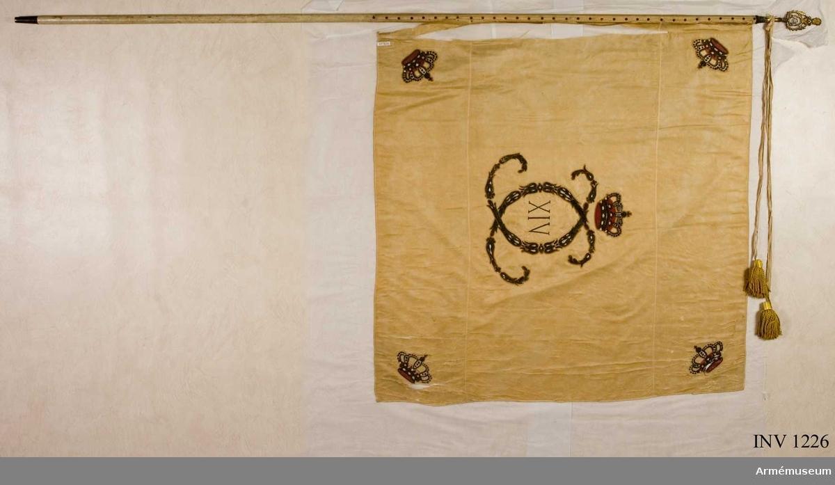 """Duk: På det gulvita kyprade fansidenet sitter i mitten ett broderat monogram föreställande två motställda """"C"""" inneslutande """"XIV"""". Broderiet utfört i plattsöm med silke och silvertråd.   Ovanför monogrammet sitter en kunglig krona utförd i plattsöm med foder i rött silke. I fanans hörn sitter snedställda kronor i rött silke.  Stång: Gulvitmålad.  Kravatt: Den lilla del som återstår är uppsydd på ett bomullsband.  Fanspets: Har Karl XIV Johans monogram, den är dock mycket ärgad."""