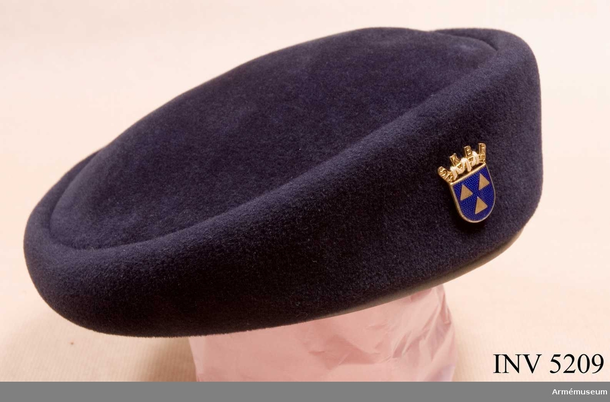 Filt. Storlek: 57. Barett 1950 för kvinnlig bilkårist till parad. Av mörkt blå  velourfilt, med läderskoning i överensstämmande färg. Användes  till parad. På vänster sida försvarsgrenstecken, SKBH:s  föreningstecken m/1942. Platta i blå emalj med förgyllda  trianglar och bokstäver.Se AM meddelanden 1967-77, XXXVII s 61.