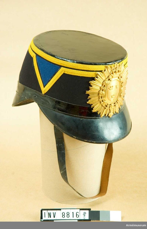 Med mörkblått kläde, galoner av gult redgarn och vid sidorna mellanblå chevron. Vapenplåt av mässing. H.fram 100 mm. H.Bak 130 mm. H.bak 130 mm.