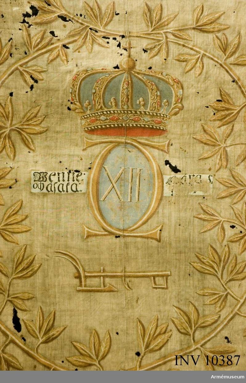 Grupp B I. Uppbådsfana för Åsaka socken, Väne härad, Västergötland. Fanduk av ofärgad lärft, med målade emblem lika på båda sidor: Karl XII:s namnchiffer, dubbelt C, varinom XII på blå botten, övrigt i gult med vita dagrar och bruna skuggor däröver sluten kunglig krona i gult med rött inner- och blått ytterfoder samt röda och blå stenar, därunder en plog; på ömse sidor om  namnchiffret i svart på vit botten Wenne: - Härad:/och Åsaka - k.p; allt omgivet av lagerkrans med rikt bladverk i gult, vitt och brunt, nedtill hopbunden med bandrosett. Fäst med grönt linneband och stora, flata mässingsstift. Stång av brunmålad furu. Spets saknas.