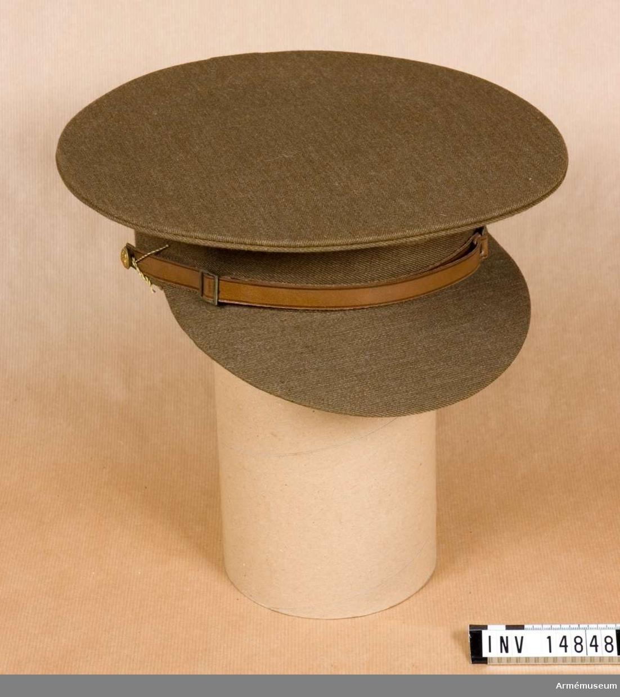 """Grupp C I. Uniformsmössa, brun. Förmodad gåva från K.A.I.D. modellkammare. Mössa av khakifärgat diagonaltyg, försedd med ett 4,5 cm brett bräm och en kulle av samma tyg med två lufthål. Hakremmar av brunt läder knäppta till mössan med två guldfärgade metallknappar. På dessa knappar finns engelska statsvapnet. Fodret av svart vaxduk med stämpel: """"J. Compton Son & Swebb Et. London"""" """"1928"""", """"W"""" följt av uppåtriktad pil under """"D"""", sedan """"D"""", """"7"""". Skärm av samma khakityg med grönt vaxduksfoder. Litteratur: Handbuch der Uniformkunde. Prof. R. Knötel, Hamburg 1937 sid 203. Från mitten av 1870-talet och under boerkriget lärde sig engelsmännen nyttan av khakiuniformer. Samtidigt med khakiuniformen infördes mössan (tallriksmodell) med skärm av kläde. Knapparna gjordes av mattbrons. Armeenalbum II: Die Englische Armée und Marine. Uniformen im Kriege. Die Englische Armée. Verlag von M. Ruhl sid 13. Som huvudbonad användes mest mössan (tallriksmodell) av khakityg. Enligt kapten W. Granberg."""