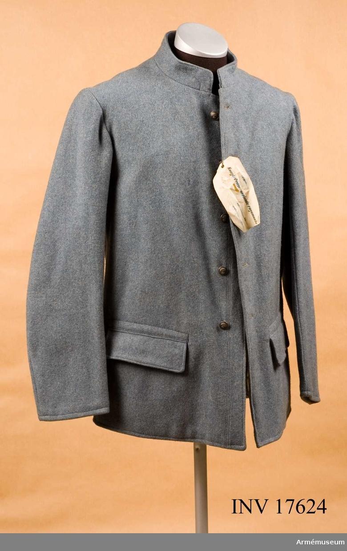 """Grupp C I. Vapenrock (på franska vareuse) av gråblått kläde, enradig med  fem knappar. På sidor finns sprund, 20 cm långt med järnknapp. På baksidan, vänster om midjan, en livremshållare av kläde med läderfoder och knapp. Två sidofickor med fyrkantiga lock, 16 cm breda. Foder av vitt tyg med två inre sidofickor. På fodret finns många stämplar; ryggsidan: """"C 3"""", """"44 102 62"""", oval rund """"1918-07-20"""", """"Commission de réception"""", rund: oläslig, """"...Paris 1918"""". Knapparna är alla av metall, gråfärgade med flammande granater, 1,8 cm i diameter; fem på framsidan, en på livremshållaren, två av järn vid spunden. Kragen är upprättstående, 4 cm hög, med runda vinklar, hyska och hake. Klaffar och nummer saknas.  LITT   Handbuch der Uniformenkunde R. Knötel, Hamburg 1937  sida 161. Efter stora förluster under krigets börjar, infördes år 1915 vid franska armén en ny uniform av gråblå färg (horisontblå).Vapenrocken hade till en början sex knappar, senare fem, två sidofickor, med upprättstående krage.Inga  axelklaffar och ärmuppslag. Arméenalbum IV Die Französische Armée. Sid 4 Leipzig. Verlag von Moritz Ruhl. Den nya franska fältuniformen av gråblått kläde infördes vid franska infanteriet i december år 1914.  I början av kriget hade vapenrocken fyra fickor  (två bröst-och två sidofickor) men senare (år 1918) endast två sidofickor. Dessa saknade knappar."""