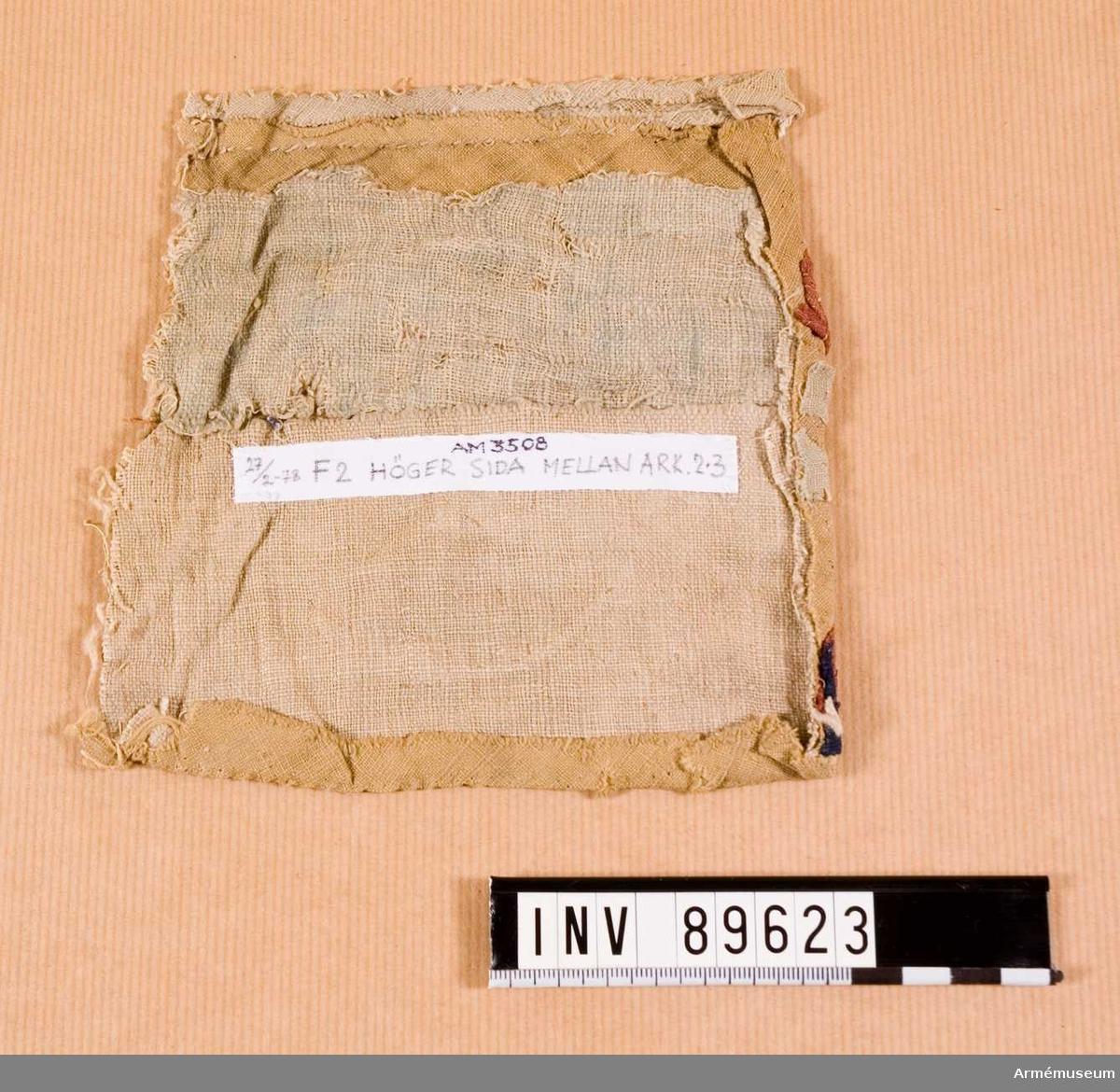 """Grupp A. Tältet är tillverkat av tre lager duk, ett yttre av   ursprungligen grön linnelärft, ett mellanskikt av röd, tät  bomullsväv, synlig som mörkare fläckar på bilden, och ett  innertält av röd linneväv. Den rika inre dekoren är utförd i applikationsarbete med upp till fem olika lager linne på botten av siden. Man har i interiören följt den turkiska arkitekturen och försökt efterlikna arkader såväl på sidostycken som i tak. De 18 arkaderna på tältets sidostycken liksom de 28 i takets  underdel är utförda i gult siden med applicerade blomvasmotiv. I  arkadöppningarnas medaljonger och kartuscher syns applicerad   blomsterornamentik av linne på växelvis grönt och gult siden   samt detaljer av förgyllt läder. På den i ögonhöjd liggande   kartuschen syns fortfarande fragment av en tidigare applikation   i gyllenläder med ytterkonturer av svart silke. De mot tältryggen på var sin sida stående elva rektangulära fälten har liksom de sex trapetsformade fälten vid kortsidorna väl bevarat sin blomsterornamentik och lysande färg. Tak och väggar knäpps   ihop med öglor av tåg på träknapar. Under varje """"pelare"""" i   arkaderna sitter tre osynligt monterade plattor av läder, 4 x 4  cm., där repen för tältets resande varit monterade. Endast vid tältöppningen finns dessa rep bevarade, i övrigt har   påfrestningen på yttertältet varit så stor att det vid dessa  punkter förslitits. Vid en under mitten av 1800-talet verkställd  reparation har emellertid alla trasiga kantpartier vikt in och   sytts ned av mot det mellanliggande mycket kraftiga och tåliga   bomullstyget, vilket ännu behållit sin klara färg och nu verkar  som påsydda lappar.  Mikroskopiering utförd på 1970-talet visade att även ytter- och innertälten var tillverkade av bomullslärft och inte av linnelärft. Se Klingberg, Wallenborg, Andersson Konservering av ett blommande turkiskt 1600-talstält s. 15.                                          /LES 20170320. 20"""