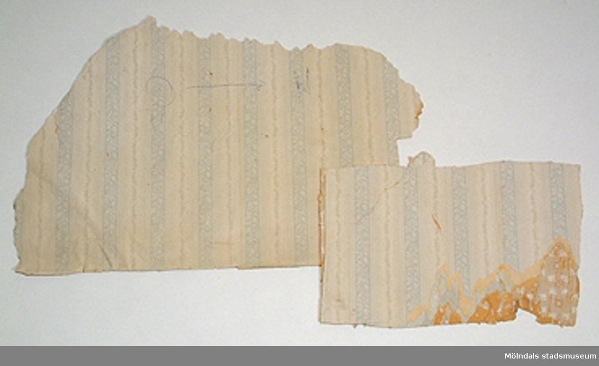 Ett stort medaljongmönster i ljusgrått och vinrött (?) på ett ofärgat papper. Tapeten delvis blekt.