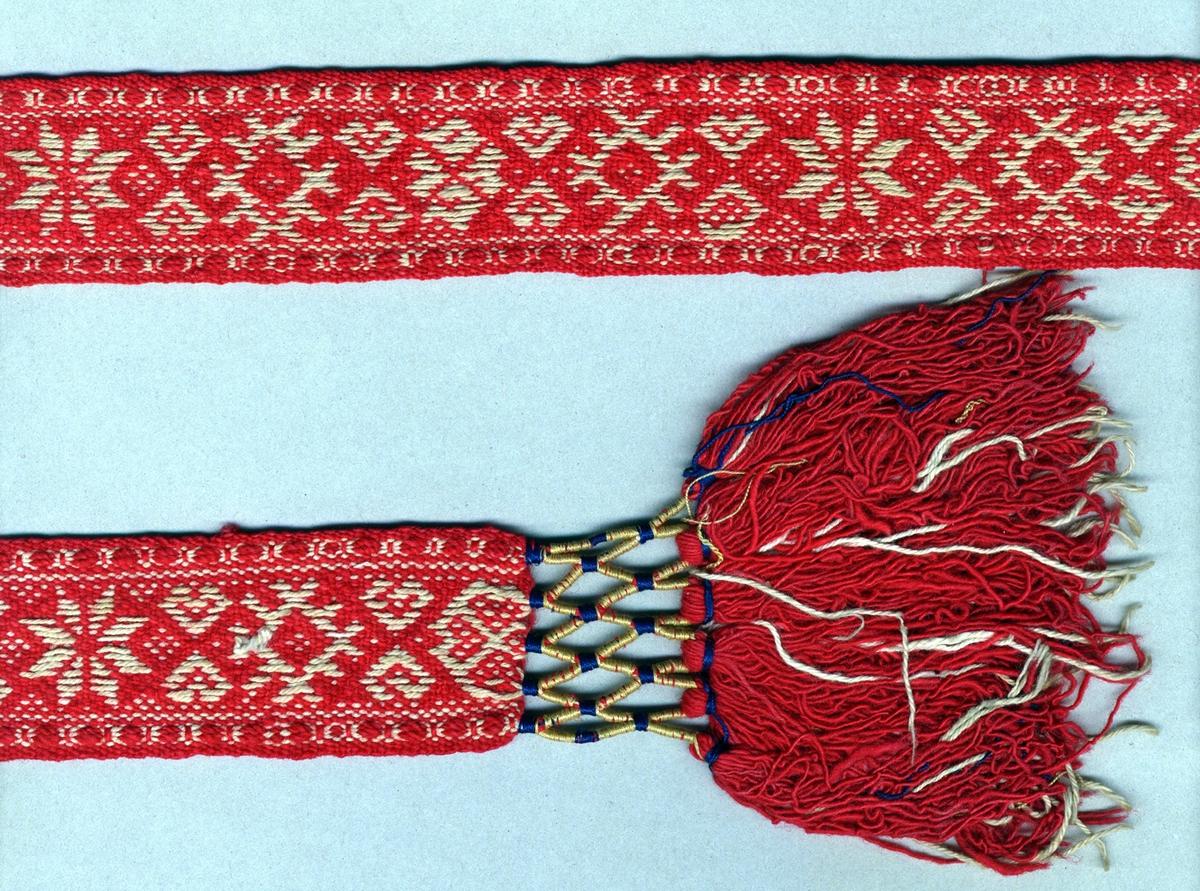 """Livband i röt  och vitt vävt i opphämta. Avslutat i var ände med tofsar (110 mm långa); varptrådarna är omlindade med blått och gult silkegarn vari frans av rött ullgarn och oblekt bomullsgarn är iknuten. Varp, botten i rött 2-trådigt z-tvinnat ullgarn. Varp, mönster i oblekt 3-trådigt s-tvinnat bomullsgarn. Två bottenvarptrådar mellan varje mönstervarptråd. Inslag i rött 1-trådigt s-spunnet ullgarn.Märkt med påsydd tyglapp med texten: """"N° 38 a Inköpt af Landstinget"""". Dessutom märkt med påsytt tygband med texten: """"SVENSK SLÖJD Malmöhus hemslöjd MALMÖ"""".Längd inklusive tofsar."""