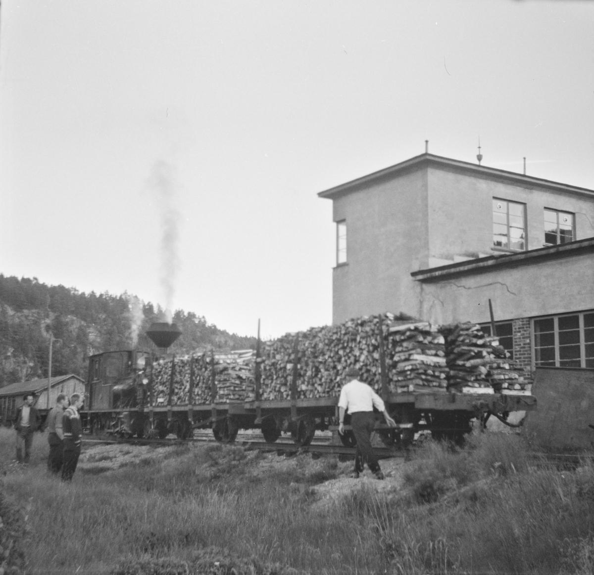 Godsvogner lastet med ved utenfor Setesdalsbanens verksted på Grovane. I bakgrunnen damplokomotiv type XXI nr. 2.
