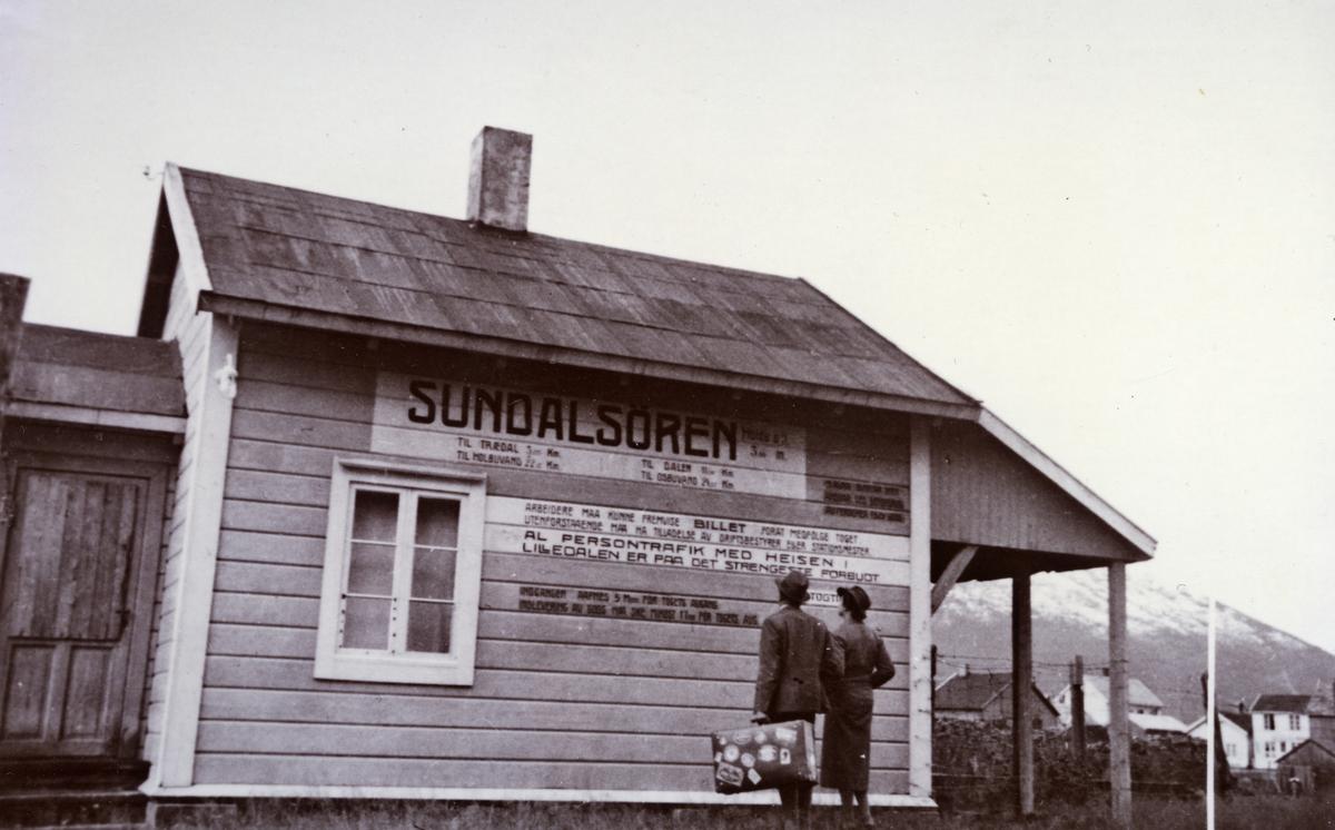 Sunndalsøren stasjonsbygning. Reisende venter på toget.