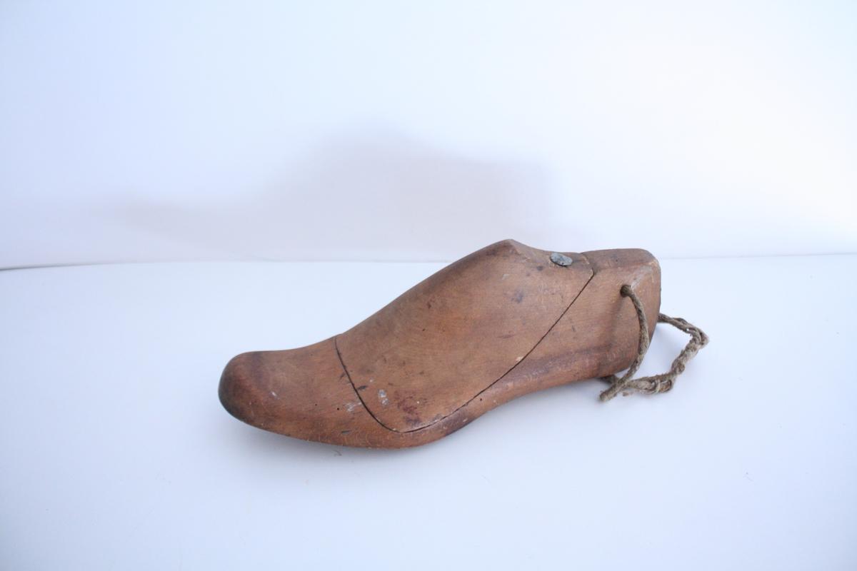 En venstre skoform. Skoformen er todel, der vristen er et løst stykke som holdes på plass med en spiker. Et tynt tau er festet gjennom et hull på hælen.