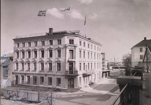 Bygate med hotellbygning i historisme. Fire -etasjes murbygning tv. med tre flaggstenger på taket. 1930 årene. Arendal, hotell Phønix.