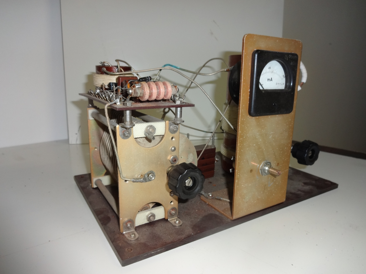 Radioapparat, muligens hjemmelaget, uten kasse. Består av variabel kondensator, spoler, små motstander og dioder og et milliampermeter. Montert på en bakelittplate.