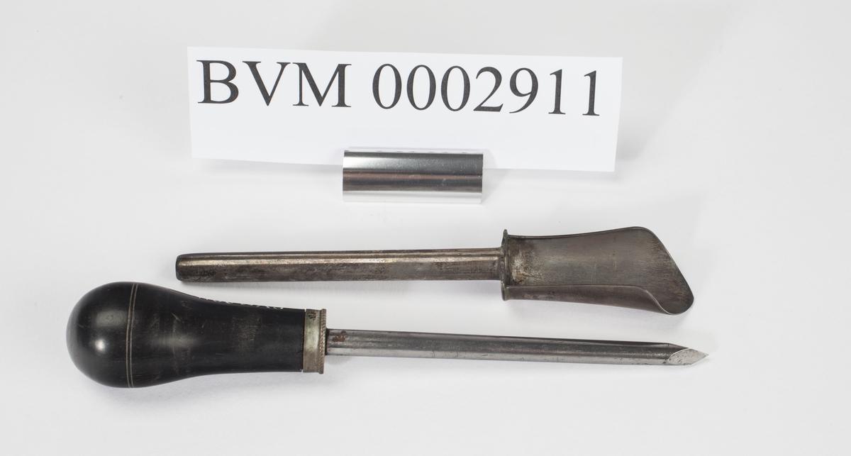 Syllignende redskap i stål med skaft av tre. I tillegg en stålsylinder med en skeilignende ende for å tømme puss fra sår og byller.