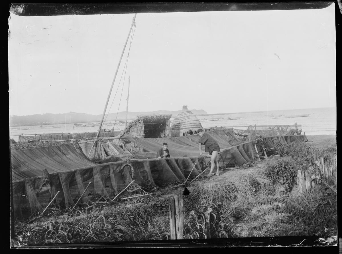 Fra Asia. Fiskegarn henger til tørk. To personer står ved garnene. To stråhytter. I bakgrunnen hav med mange båter.