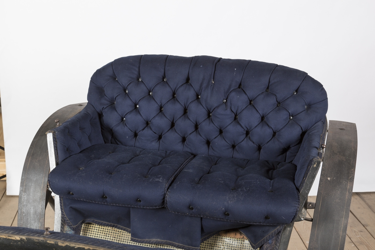 Bak- sete, motsete og kuskesete er trukket med blått stoff og kantet m/blått ullbånd. Setene er polstret. Baksetet har knapper i rygg og på setet.  Over fatingen er det festet et lær- trekk som er fòret m/blått ullstoff.
