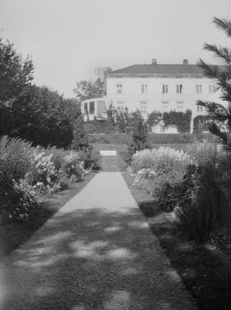 Terrassehage med trapper, stier og hekker og andre hagevekster på Linderud Gård i blomstringstiden. I bakgrunnen hovedhuset.