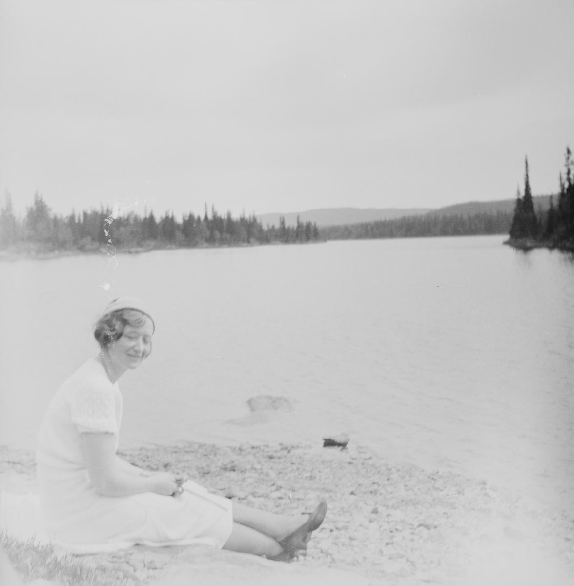 En kvinne sitter på en steinete strand ved en innsjø i Jeppedalen. I bakgrunnen ligger skogkledte nes og åser.