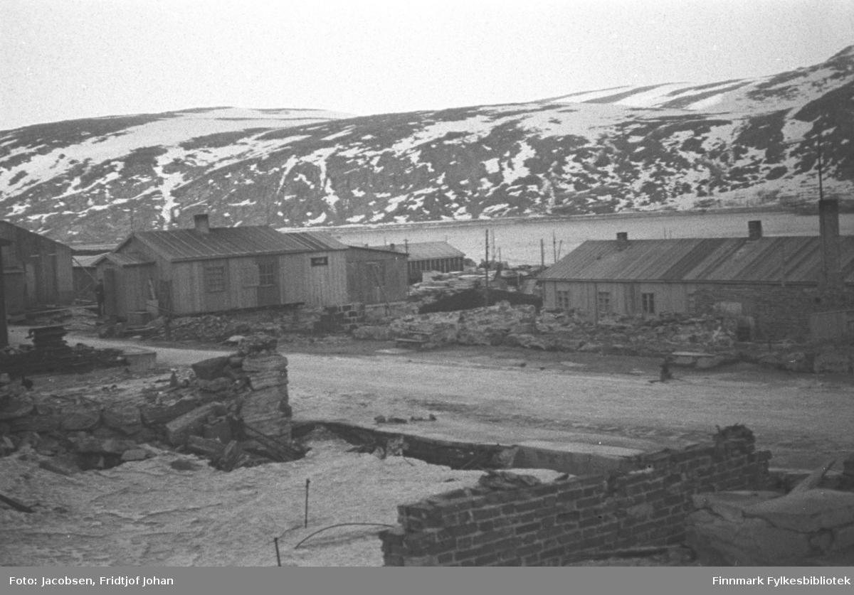 Ruiner og brakker i Storgata i Hammerfest sentrum. Rester av en grunnmur står nederst å bildet. En kai med en havnebygning ses midt på bildet. Ved kaia ligger en båt. De delvis snødekte fjellene på bildet er Fuglenesfjell til venstre og til høyre er begynnelsen av Mollafjell. Sjøen som ses på bildet er deler av Hammerfest havn og innseilinga til byen. Bildet er nok tatt sent på vinteren eller tidlig på våren.